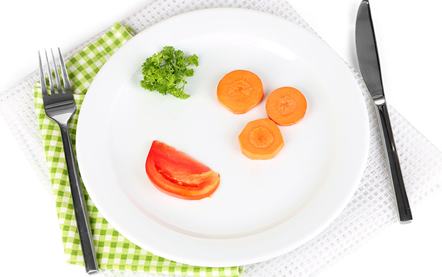 Small portion of food on big plate isolated on white